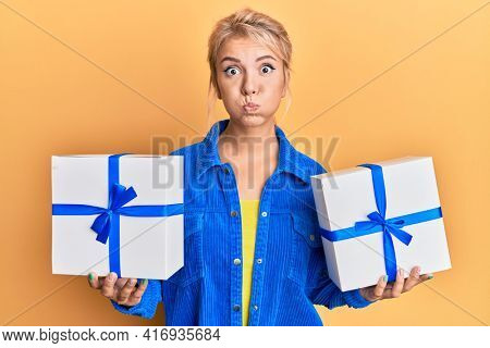 Young blonde girl holding gifts puffing cheeks with funny face. mouth inflated with air, catching air.