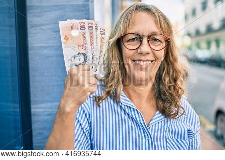 Middle age caucasian woman smiling happy holding uk pounds banknotes standing at the city.