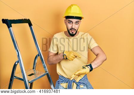 Handsome man with beard by construction stairs wearing hardhat in hurry pointing to watch time, impatience, upset and angry for deadline delay