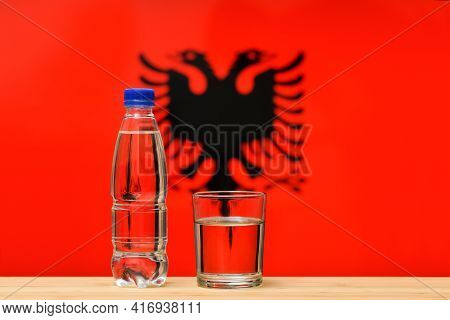 A Bottle Of Clean Drinking Water And A Glass Stand On The Table Against The Background Of The Flag O