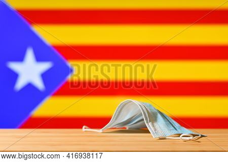 A Medical Mask Lies On The Table Against The Background Of The Flag Of Catalonia. The Concept Of A M