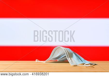 A Medical Mask Lies On The Table Against The Background Of The Flag Of Austria. The Concept Of A Man
