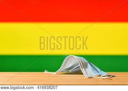 A Medical Mask Lies On The Table Against The Background Of The Bolivian Flag. The Concept Of A Manda