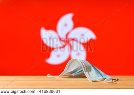A Medical Mask Lies On The Table Against The Background Of The Flag Of Hong Kong. The Concept Of A M