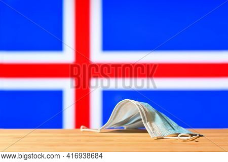 A Medical Mask Lies On The Table Against The Background Of The Flag Of Iceland. The Concept Of A Man