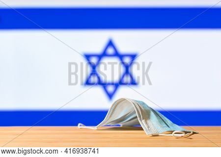 A Medical Mask Lies On The Table Against The Background Of The Flag Of Israel. The Concept Of A Mand