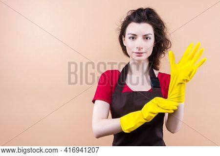 Young Brunette Woman With Curly Hair Wearing Cleaner Apron And Rubber Yellow Gloves Isolated On Beig