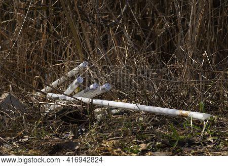 Broken Fluorescent Lights On The Dry Grass.criminal Disposal Of Fluorescent Mercury Lamps .environme