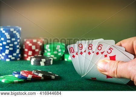 Poker Cards With Straight Flush Combination. Close Up Of Gambler Hand Takes Playing Cards In Poker C