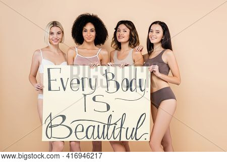 Cheerful Multiethnic Women Holding Placard With Every Body Is Beautiful Lettering On Beige.