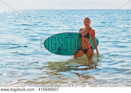 Adventure Trip Concept. Fit Girl In Swimsuit With Surfboard. Sunny Day On Sandy Seashore. Summer Tim