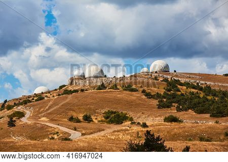 Technology And Research Station Concept. Complex Building Standing On Hill. Dark Stormy Sky. Mountai