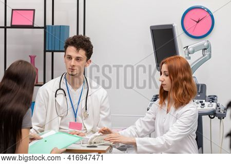 After Blood Pressure Checks, A Smiling Doctor Reassures A Patient And An Intern Folds Up A Blood Pre