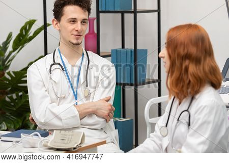 A Young Doctor Talks To A Redheaded Intern About His Next Patient. Gp. Doctors Office