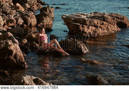 Girl Chilling In Sea Or Sunbathing Time. Beach Day And Tan. Lady In Pink Bikini. Sharp Cliffs And Oc