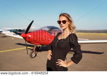 Fashionable Women In Beautiful Classy Black Dress And Beautiful Sunglasses Posing On A Red Private P