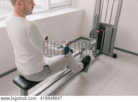 Close-up Of A Man Performing Traction On A Weight Training Machine. Intense Workout In The Gym
