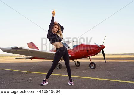 Athletic Woman Practicing Stretching Near A Red Private Plane. Working Out On The Aerodrome On Plane