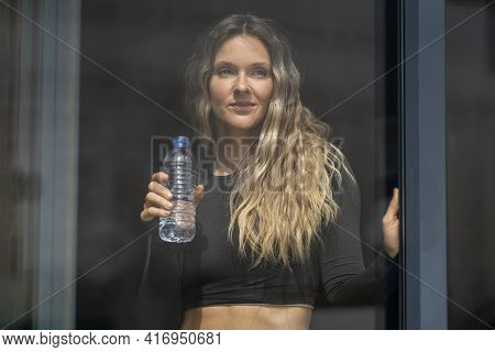 Woman In Sportswear Holding Bottle Of Drinking Water By The Window At Home. Sporty Active Attractive