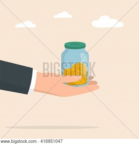 Hand With Moneybox Full Of Coins. Glass Money Jar. Saving Coin In Moneybox. Income, Savings, Investm