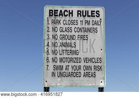 Beach Rules Sign Against A Stark, Cloudless Blue Sky.