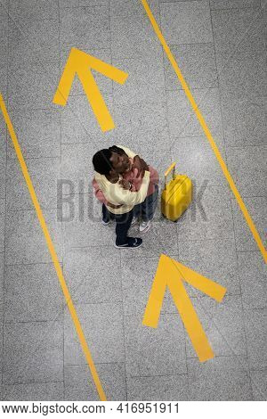 Top View Of Romantic Couple Embrace In Airport Meeting After Long Separation Due To Coronavirus Dise