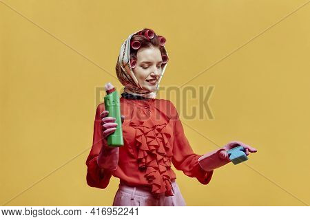 A Young Cleaning Lady Is Holding A Sponge And A Bottle Of Cleaning Agent.