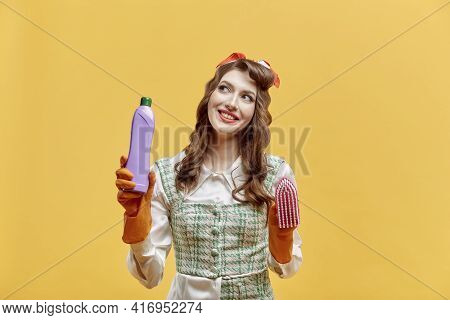 A Female Cleaner Holds Tools For Cleaning The House. Yellow Background.