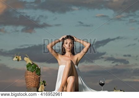 Sexy Girl In White Sexy Dress Denuded Gorgeous Body With Red Wine Glass Wicker Bottle And Vine On Ev