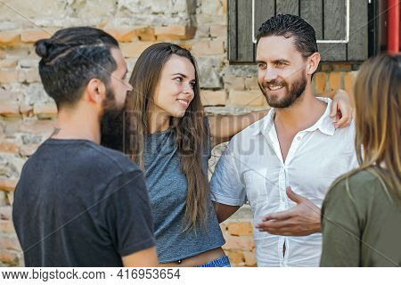 Smilling Couple With Friends Outdoor On Stony Wall Background
