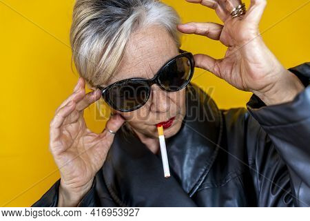 Funny Portrait Of Mature Woman. Sophisticated Lady Having Fun Dressed In A Leather Coat Smoking A Ci