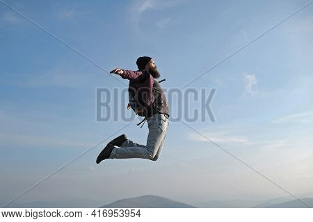 Man Hipster Jumps With Backpack. Carefree Happiness Freedom Concept. Hipster Man With Beard And Mous