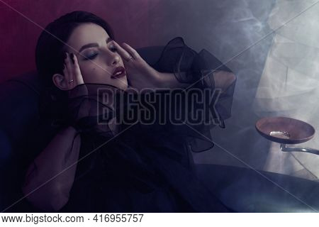 Portrait of a beautiful brunette young woman with closed eyes in a luxury apartment in smoke. Beauty, fashion concept. Glamorous lifestyle.