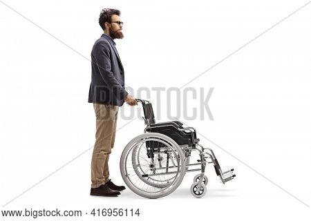 Full length profile shot of a bearded man pushing an empty wheelchair isolated on white background