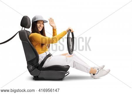 Young female driving with a seatbelt waving at camera isolated on white background