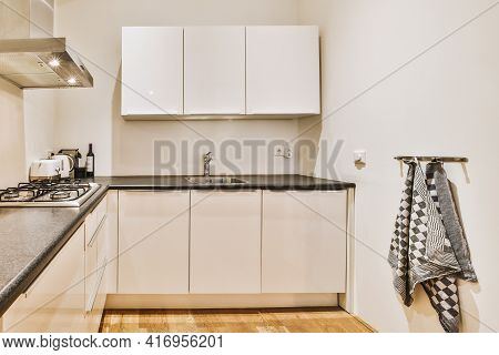 Fragment Of Interior Of Light Narrow Home Kitchen With Minimalist Style White Furniture With Sink An