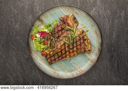 Grilled Beef Steak With Rosemary, Salt And Pepper On Black Stone Plate. Grilled Striploin Sliced Ste