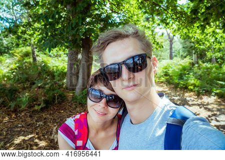 Romantic Couple In Sunglasses Making Selfie While Walking In The Summer Forest. Local Traveling And