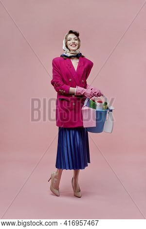 A Beautiful Woman Holds A Bucket Of Cleaning Tools In Her Hands. Bright Makeup.