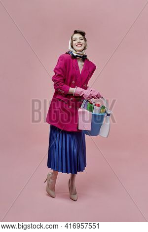 A Satisfied Woman Holds A Bucket Of Cleaning Tools In Her Hands, Full-length.