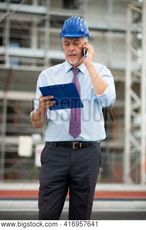 Senior architect talking on the phone outdoors in front of a construction site