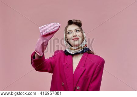 A Woman Wearing Gloves Is Holding A Brush To Clean The Joints Between The Tiles.
