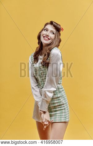 A Young Happy Woman With Bright Makeup In A Short Plaid Dress. Long, Wavy Hair.