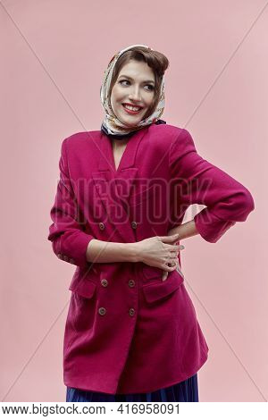A Happy Young Woman In Pin-up Style With Bright Makeup In A Pink Jacket.