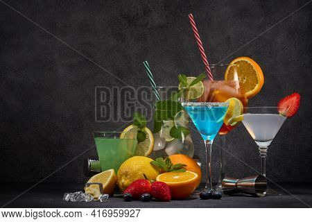 Cocktails set. Glasses with various cold colorful  beverages, fruits and bar tools on dark grey background with copy space. Weekend or holiday party. Cocktail bar