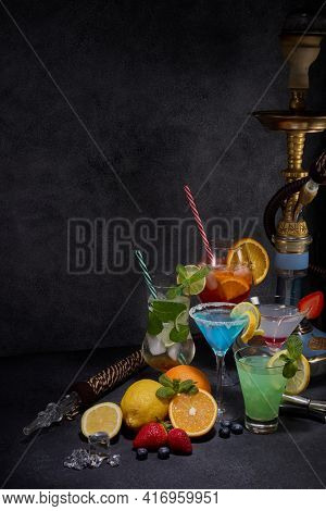 Hookah and cocktails set. Glasses with various cold  beverages, fruits, shisha and bar tools on dark grey background. Weekend or holiday party. Hookah bar, cocktail bar.