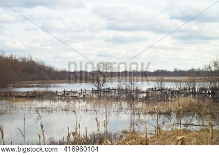April Cloudy Landscape In Flood Of The River. Spring Flood. Flooding Meadows Farms Yard Fence And Ga