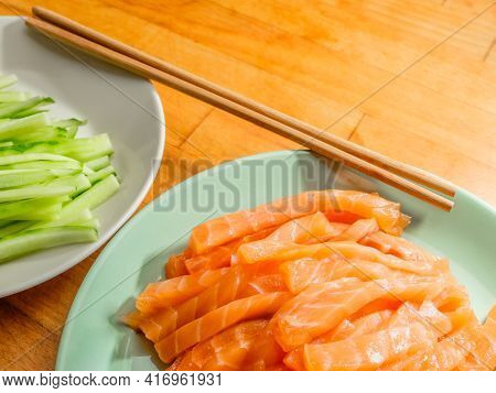 Selective Focus On Salmon And Fresh Cucumber Slices On Plates And Bamboo Chopsticks. Flat Lay. Appet