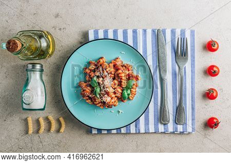 Composition With Plate Of Pasta, Tomato, Basil, Salt, Olive Oil, Napkin And Cutlery On A Stone Backg