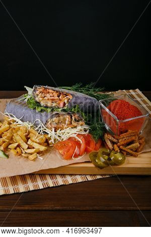 Fresh Hot Fragrant Shawarma Cut Lies On A Wooden Board With Vegetables, Green Leaves And Fries